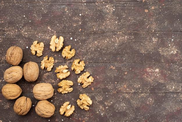 Взгляд сверху свежие целые грецкие орехи изолированные на коричневой древесине