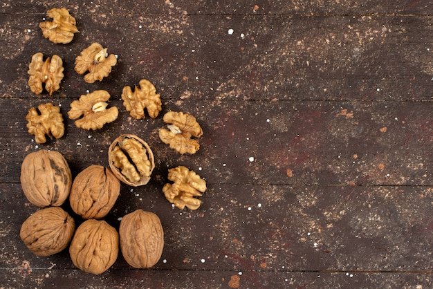 Вид сверху свежие целые грецкие орехи сырые на коричневый