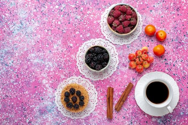 ピンクの机の上に小さなケーキとお茶と新鮮な野生のベリーラズベリーとブラックベリーの上面図。