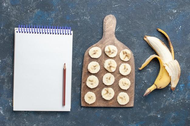 Vista dall'alto di banana gialla fresca dolce e deliziosa sbucciata e affettata con blocco note sulla scrivania scura, frutta a bacca dolce vitamina salute