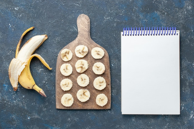Top view of fresh yellow banana sweet and delicious peeled out and sliced with notepad on dark desk, fruit berry sweet vitamine health