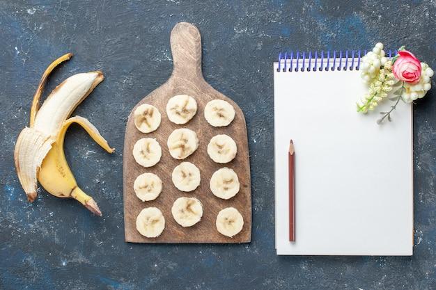 Vista dall'alto della banana gialla fresca dolce e deliziosa sbucciata e affettata con blocco note sul buio, bacche di frutta dolce vitamina salute