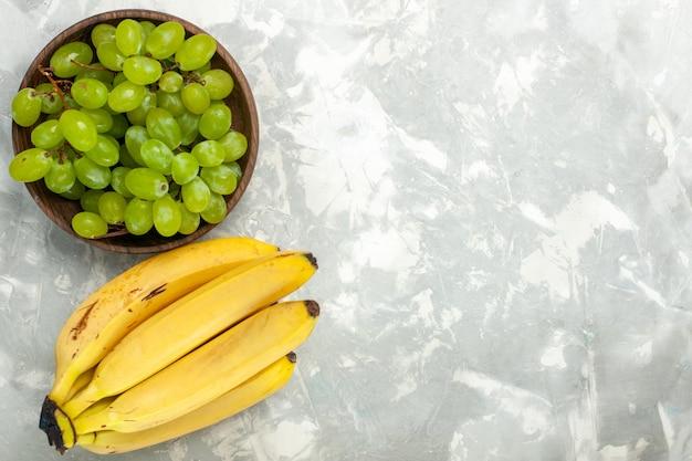 Вид сверху свежие желтые бананы, спелые и вкусные фрукты с виноградом на светло-белом столе