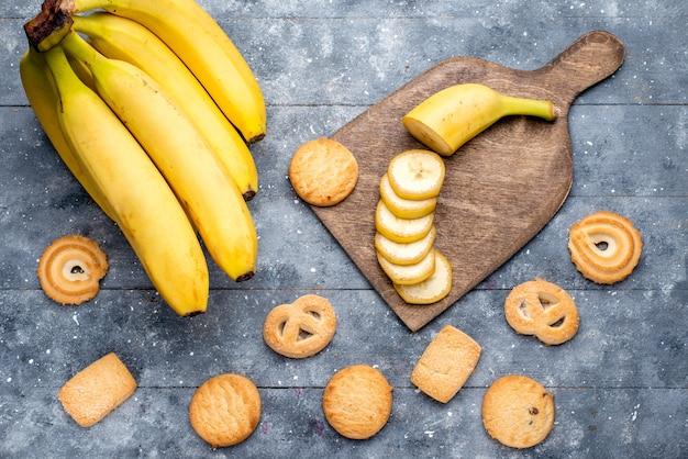 Vista dall'alto di banane fresche gialle affettate e intere insieme a biscotti su grigio, bacche di frutta fresca