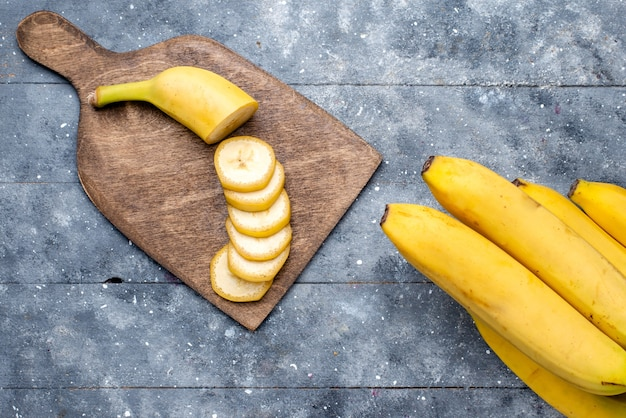 Top view of fresh yellow bananas sliced and whole on grey, fresh fruit berry