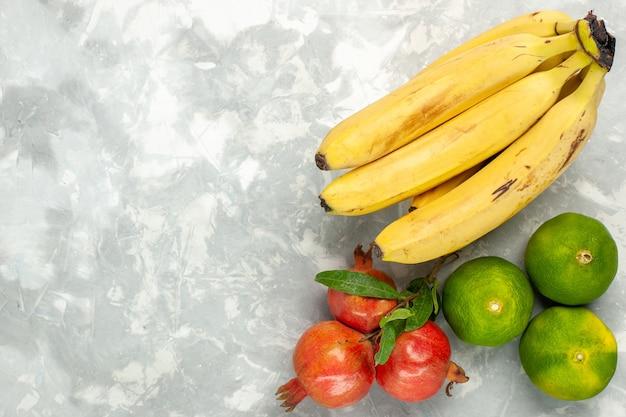 明るい白い机の上にザクロとみかんと新鮮な黄色のバナナの上面図