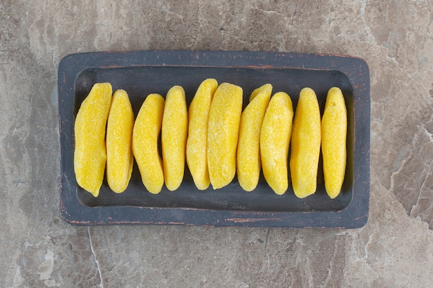 Top view of fresh yellow candies on wooden board .