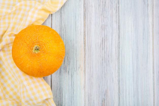 Vista dall'alto di melone cantalupo fresco e giallo con tovaglia a quadretti gialla su legno grigio con spazio di copia