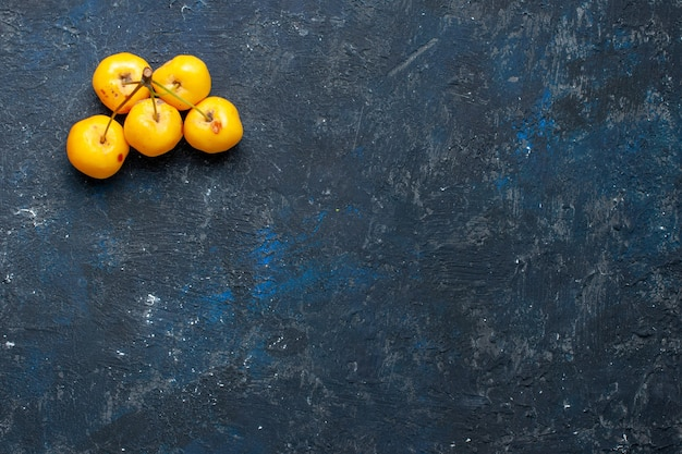 Top view of fresh yellow cherries isolated on dark desk, fruit berry fresh mellow