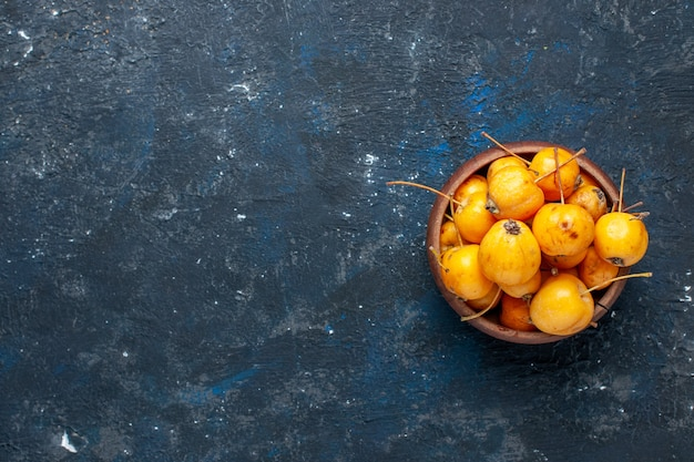 Top view of fresh yellow cherries ripe and sweet fruits on dark desk, fruit fresh mellow