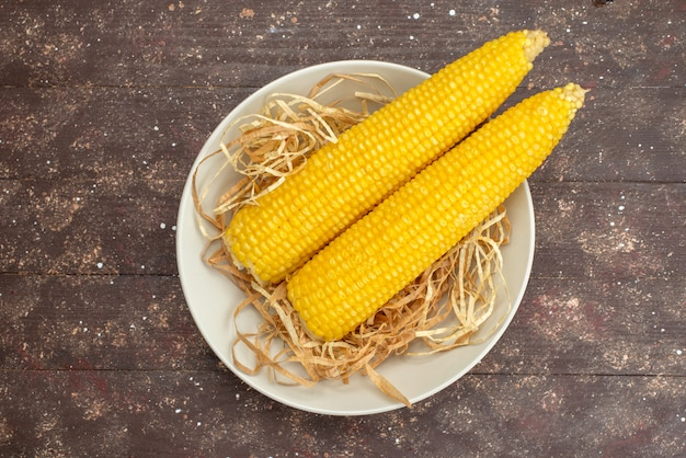 Top view fresh yellow corns inside white plate on wood