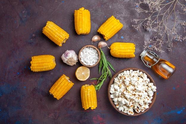 上面図新鮮な黄色いトウモロコシとポップコーンが暗い表面にあるコーンスナック食品生の新鮮な
