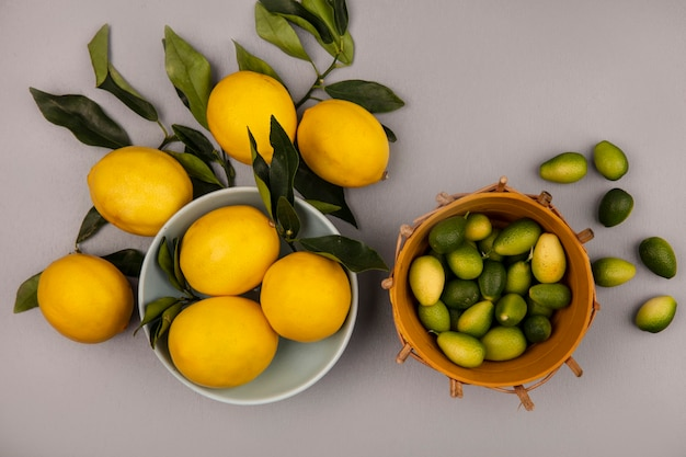Top view of fresh yellow lemons on a bowl with leaves with kinkans on a bucket with lemons isolated on a white wall
