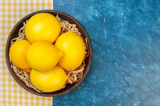 Вид сверху свежие желтые лимоны внутри тарелки на синей стене