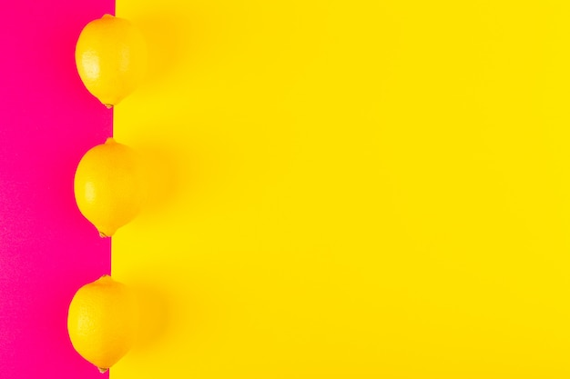 A top view fresh yellow lemons ripe juicy mellow whole lined on the pink-yellow background fruits citruses summer