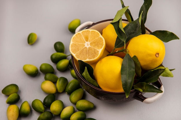 Top view of fresh yellow lemons with leaves on a bowl with kinkans isolated on a white wall