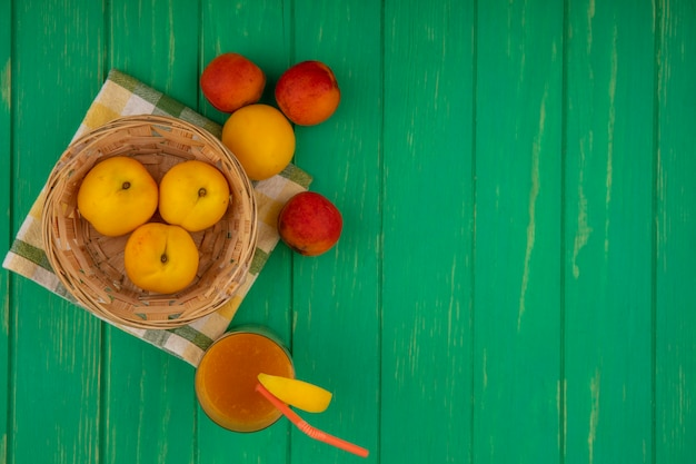 Top view of fresh yellow peaches on a bucket on a checked cloth with pinky-orange peaches with peach juice on a green background with copy space