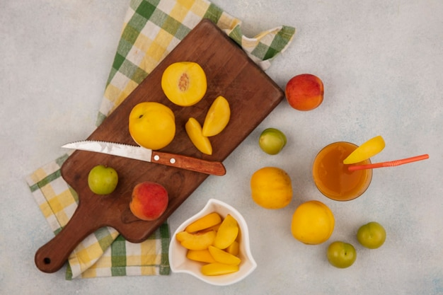 Top view of fresh yellow peaches on a wooden kitchen board with knife with chopped slices of peach on a white bowl with peach juice on a glass on a white background