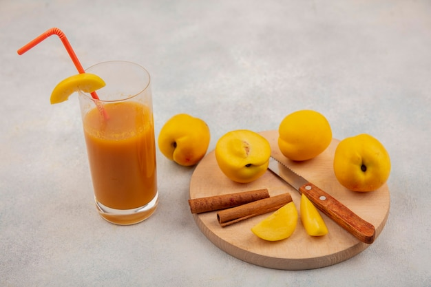Top view of fresh yellow peaches on a wooden kitchen board with knife with cinnamon sticks with fresh peach juice on a white background