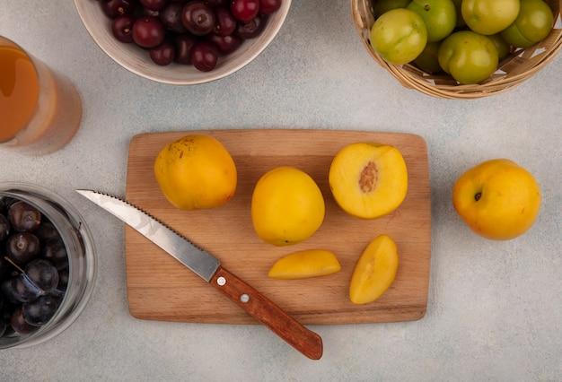 Vista dall'alto di pesche gialle fresche su una tavola da cucina in legno con coltello con prugnole viola scuro su una ciotola di vetro con prugne ciliegia verdi su un secchio su sfondo bianco