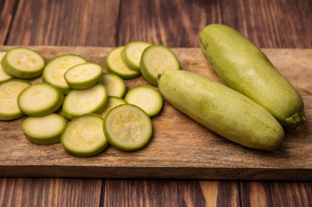 Top view of fresh zucchinis on a wooden kitchen board with zucchinis isolated on a wooden background
