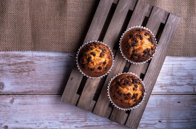 Vista dall'alto dei cupcakes appena sfornati con gocce di cioccolato su un vassoio di legno