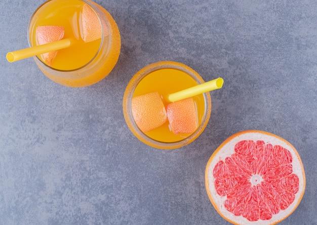 Vista dall'alto di succo d'arancia appena fatto con pompelmo maturo su sfondo grigio.