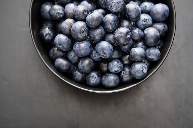 Top view of freshly picked blueberries in black bowl