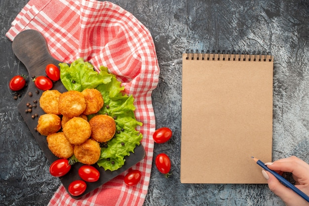 Top view fried cheese balls on cutting board pencil in female hand notepad