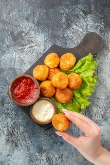 Top view fried cheese balls lettuce sauce bowls on chopping board cheese ball in female hand on table