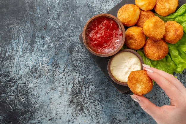 Top view fried cheese balls lettuce sauce bowls on chopping board cheese ball in woman hand on table