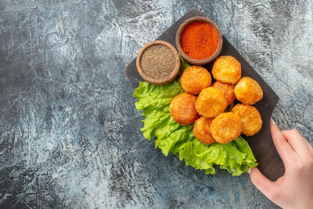 Top view fried cheese balls lettuce spice bowls on chopping board in female hand on table copy place