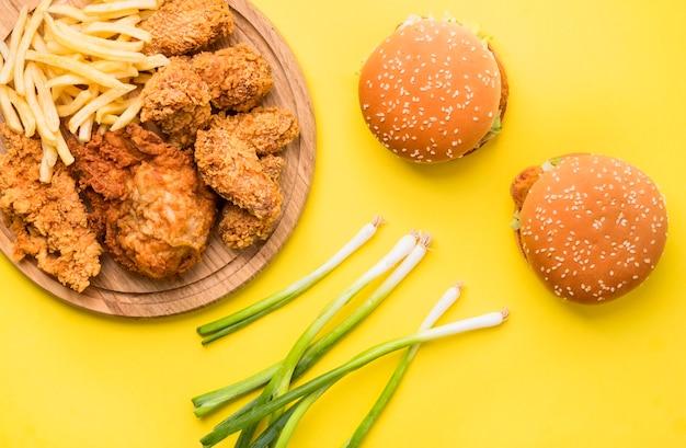 Вид сверху жареный цыпленок и гамбургеры с картофелем фри и зеленым луком