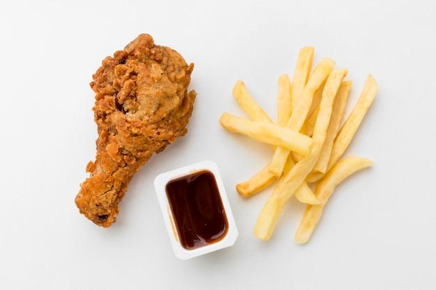 Вид сверху жареная куриная голень с картофелем фри и соусом