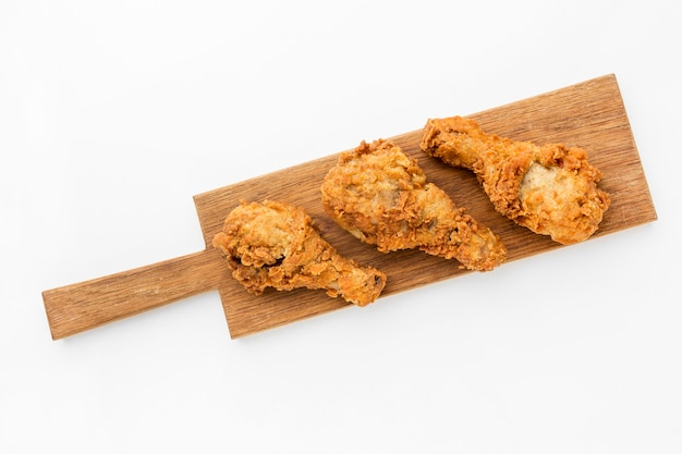 Top view fried chicken drumsticks on cutting board
