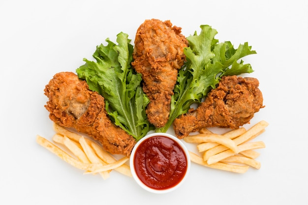 Top view fried chicken drumsticks with fries and ketchup