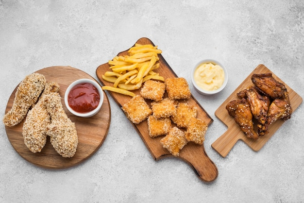 Top view of fried chicken nuggets and sauces on chopping boards