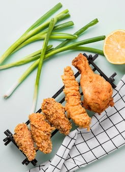 Top view fried chicken on tray with green onions, lemon and kitchen towel