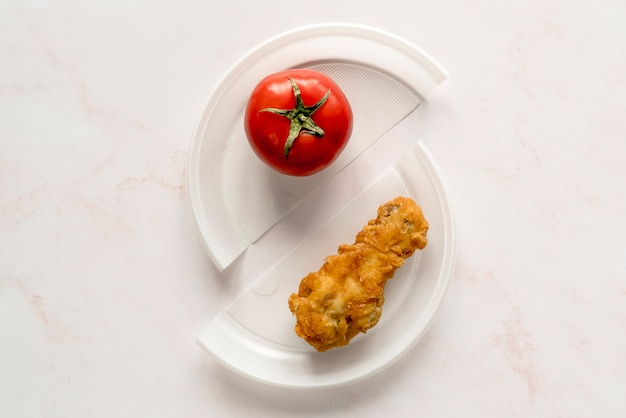 Top view of fried chicken and whole red tomato on broken plate