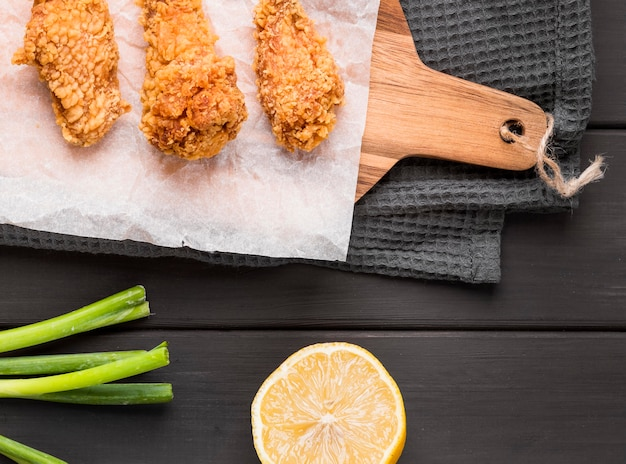 Top view fried chicken wings on cutting board with lemon and green onions