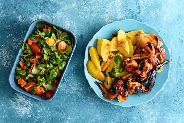Вид сверху жареные куриные крылышки в маринаде соевого соуса с картофелем и овощным салатом на синем фоне