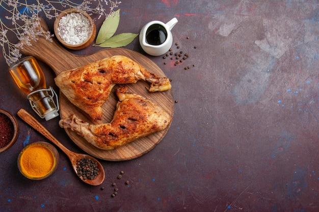 Вид сверху жареный цыпленок с разными приправами на темном пространстве