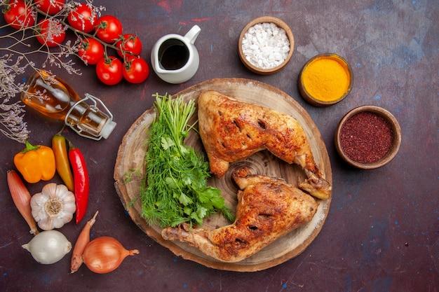 어두운 공간에 채소와 야채가 들어간 상위 뷰 프라이드 치킨