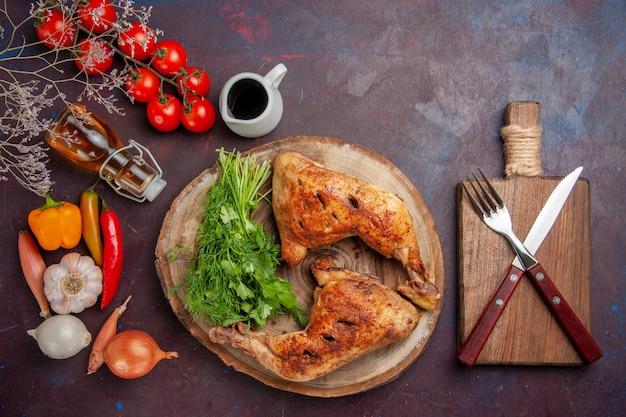Вид сверху жареный цыпленок с зеленью и овощами на темном пространстве