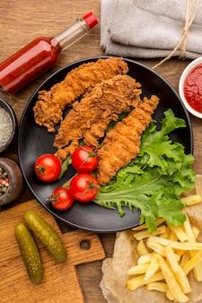 Vista dall'alto pollo fritto con pomodori e insalata sul piatto con patatine fritte