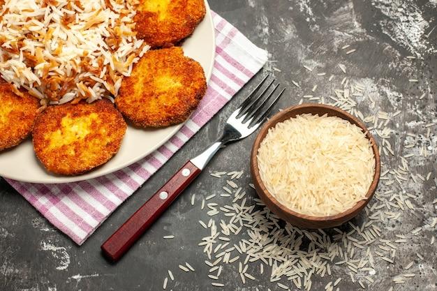 Вид сверху жареные котлеты с вареным рисом и сырым рисом на темной поверхности мясного блюда из котлеты