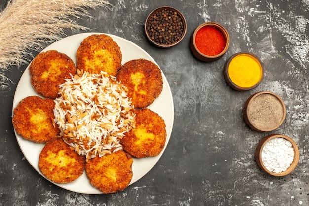 Вид сверху жареные котлеты с вареным рисом и приправами на темном мясном блюде на полу