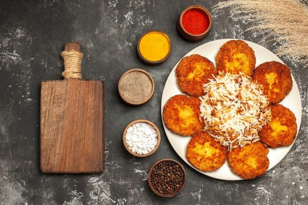 Вид сверху жареные котлеты с вареным рисом и приправами на темной поверхности блюдо фото мясо