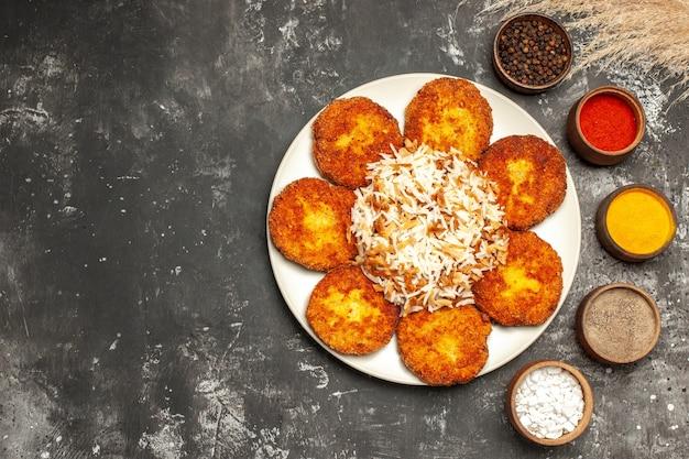 어두운 바닥 음식 접시 사진 고기에 밥과 조미료와 함께 튀긴 커틀릿 상위 뷰