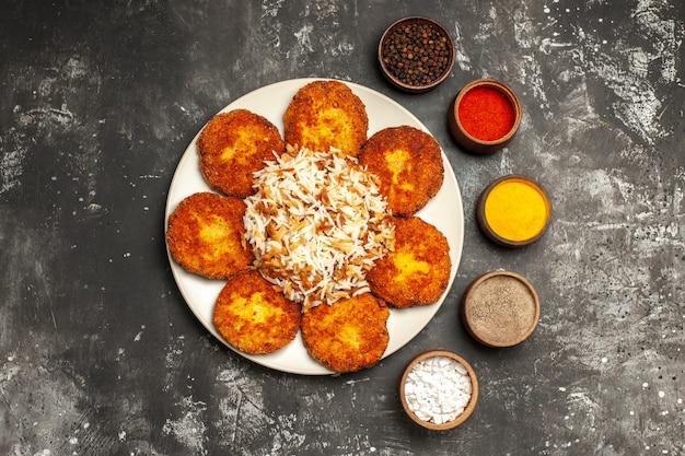어두운 표면 음식 사진 고기에 밥과 조미료를 곁들인 튀긴 커틀릿